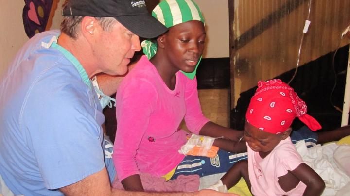 Dr Bill Frist attending a woman and her child in Haiti