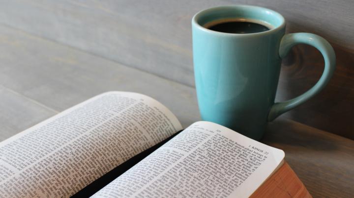 Bible with coffee mug on a table
