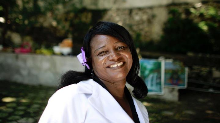 Woman in a doctor's coat smiling at the camera