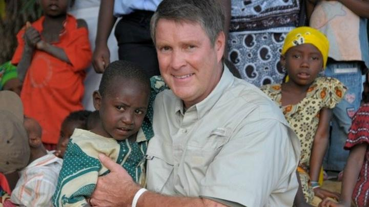 Bill Frist holding a child and smiling at the camera